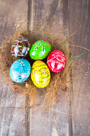 decode: Colorful easter eggs in straw nest on a wooden table