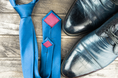 show cases: Classic men shoes and blue tie on wood background