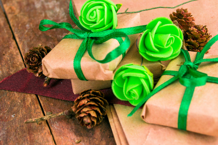 natural paper: Green presents wrapped in natural paper on old wooden background. Stock Photo
