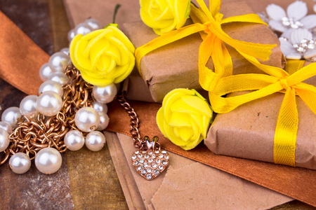 natural paper: Yellow gift box wrapped in natural paper on wooden table top view