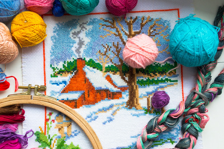 embroidered: Embroidered winter house with yarn for colour knitting and tambour Stock Photo