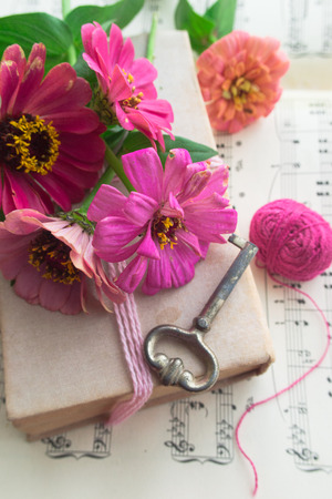 Old book with vintage key and pink flowers zinnia on music sheet background