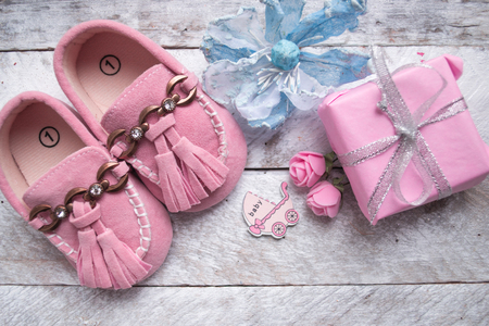 Close up of baby shoes on a wood background. Greeting card