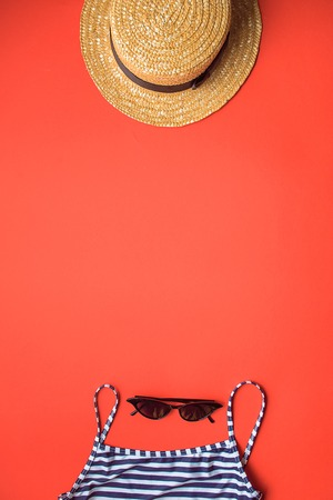 retro set of vacation on red background with copy straw hat, swimming wear.