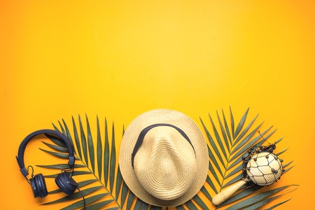 concept of man on vacation. set of straw hat and earnings on orange background