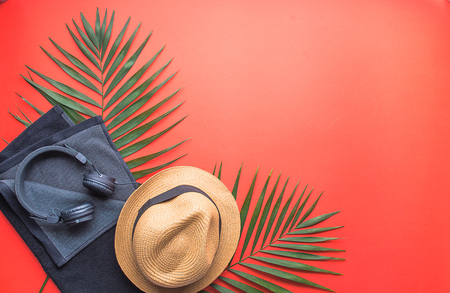 concept of man on vacation. set of straw hat, reader towel and headphone on red background 版權商用圖片