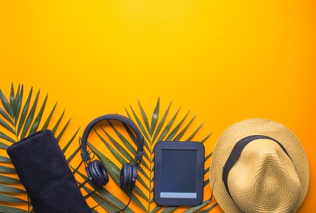 concept of man on vacation. set of straw hat, reader towel and headphone on orange background
