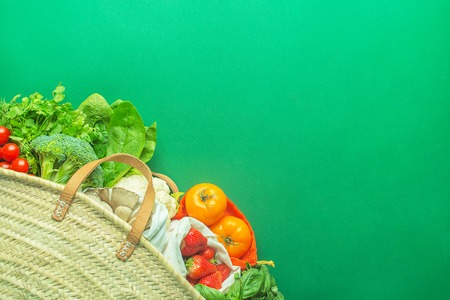 straw bag full of products without plastic backs with copy space on green background