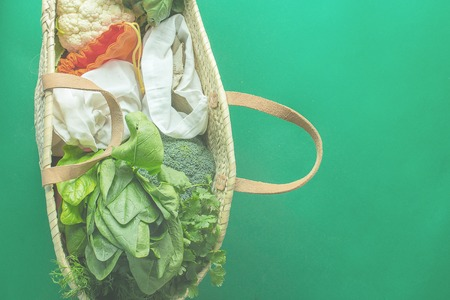 straw bag full of products without plastic backs with copy space on green background 版權商用圖片
