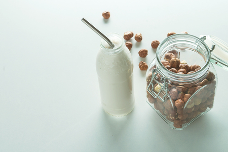 vegan milk in glass jar with ingredients on white background with copy space