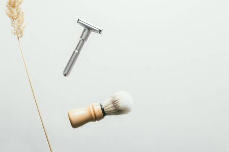 set for shaving with metal safe razor, wooden brush and soap. levitation concept flying objects Stockfoto