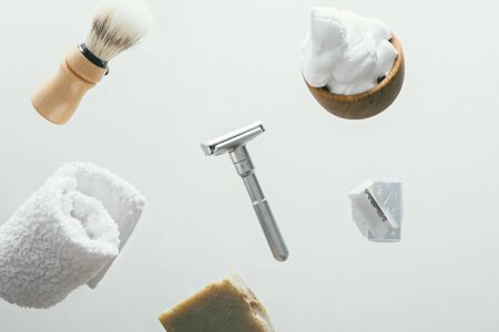set for shaving with metal safe razor, wooden brush and soap. levitation concept flying objects Banque d'images