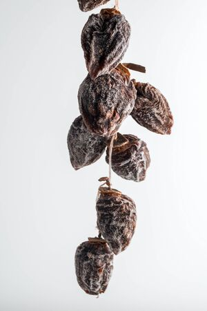 dried persimmon hanging on rope on white background