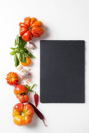 set of red organic tomatoes and spyces with black board for text