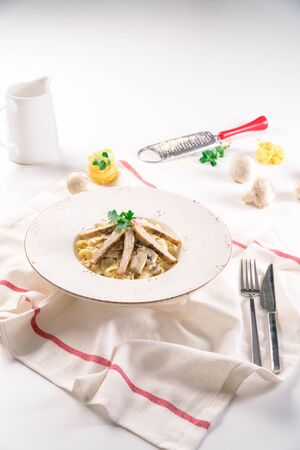Linguine Pasta with Grilled Chicken Served on a White Plate with Parsley on it