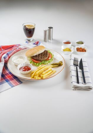 Hamburger with Fries and Pickles Served on a Plate with Sauces and Spices and Coke Stock Photo