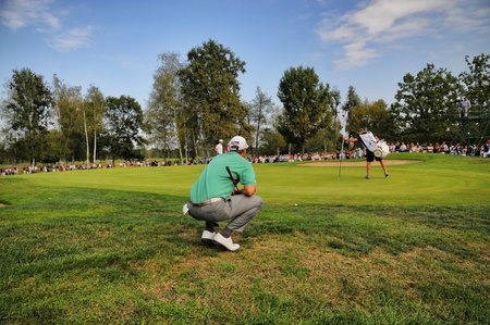 Turin Italy about September 2016 Unknown golf player concentrate seek the right line squatted on the green with wide crowd in the background Redactioneel
