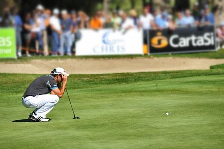 Turin Italy Unknown golf player concentrate seek the line squatted on the green with blurred crowd in the background