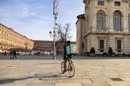 Deliveroo food delivery bike runner panoramic view in historical square logo modified by the biker to show only LIVE word Turin Italy 18 January 2018 Redakční
