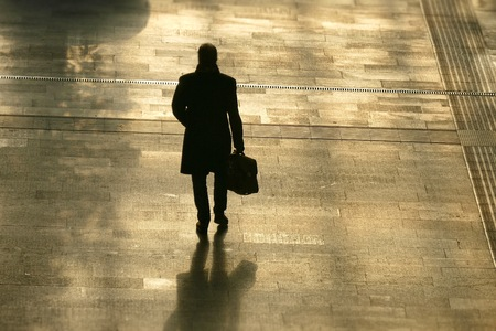 Silhouette of lonely man holding a bag walking ahead. Back view