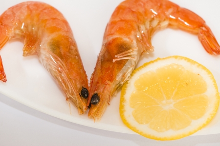 two shrimp with lemon on a plate photo