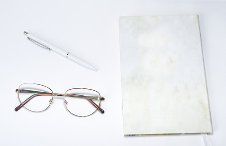 Glasses, pen and notebook on a table photo