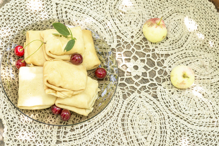 brigth: delicious pancakes with cherries on a tablecloth