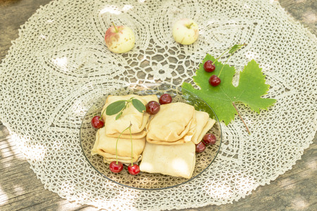 glass plate with pancakes on knitted tablecloth photo