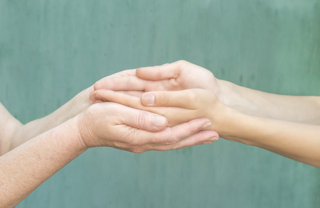 caring hands of a young girl and an old woman Stock Photo