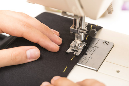 woman sews clothes on a sewing machine