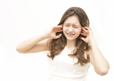 distraught woman covering her ears with her hands