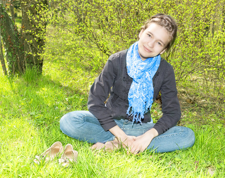 girl sitting on the grass in lotus pose photo