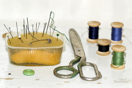 old metal needles, pins, scissors and wooden spools of thread