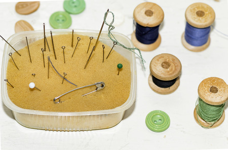 old rusty metal needles, pins and wooden spools of thread