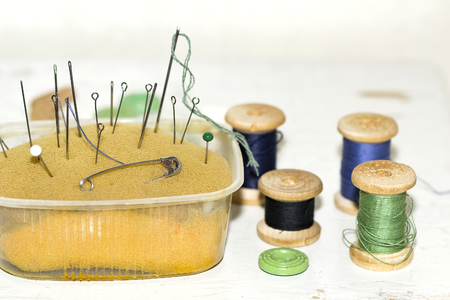 old rusty metal needles, pins in old paralon and wooden spools of thread