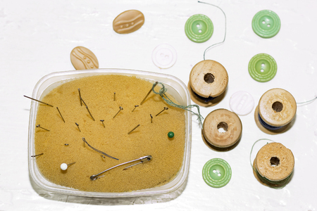 old rusty metal needles, pins, wooden spools of thread and buttons top view Banco de Imagens