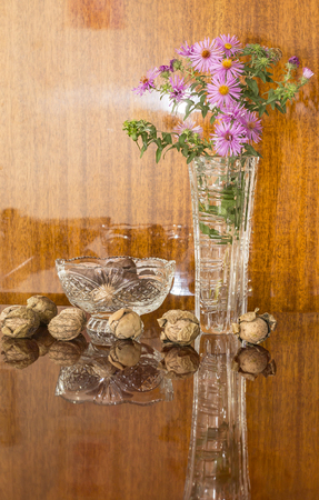 walnuts in a crystal vase and flowers Stock Photo