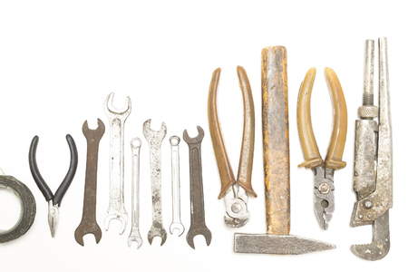 rusty and old tools arranged in a row on a white background top view