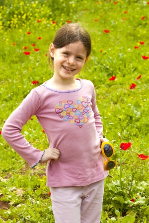 girl  in a green field with Anemone flowers photo