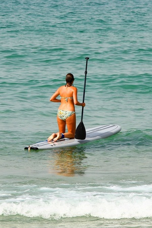 young woman on a stand up paddle board  photo