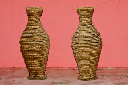 spliced: two woven vase on pink background