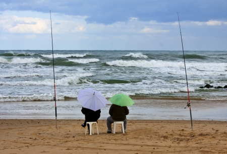 Two fishermen with umbrellas in storm photo