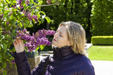 woman smelling lilac in spring park  photo