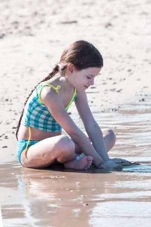 Girl playing in sand  on the beach photo