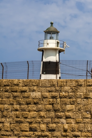 acre: lighthouse on old wall in Akko, Israel Stock Photo