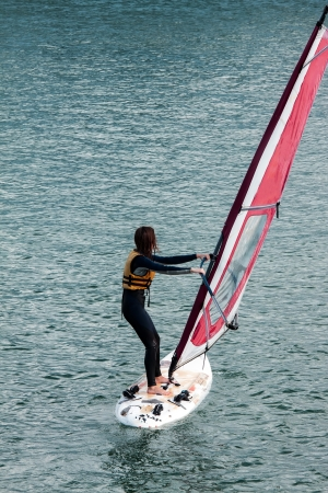 Unrecognizable person  of a windsurfer girl on the water