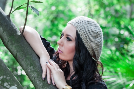 beautiful young woman in hat posing in the park photo
