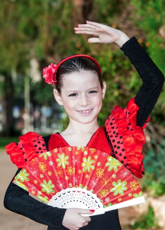 Happy little pretty girl in spanish red dress photo