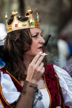 NETANYA, ISRAEL - FEBRUARY 24: Unidentified women dressed as a Queen smoking on street of Netanya during on Purim carnival February 24, 2013 in Netanya, Israel.
