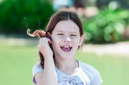 Little girl is  playing with her hair